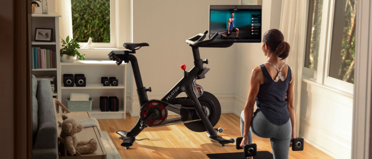 A lady exercising using Peloton