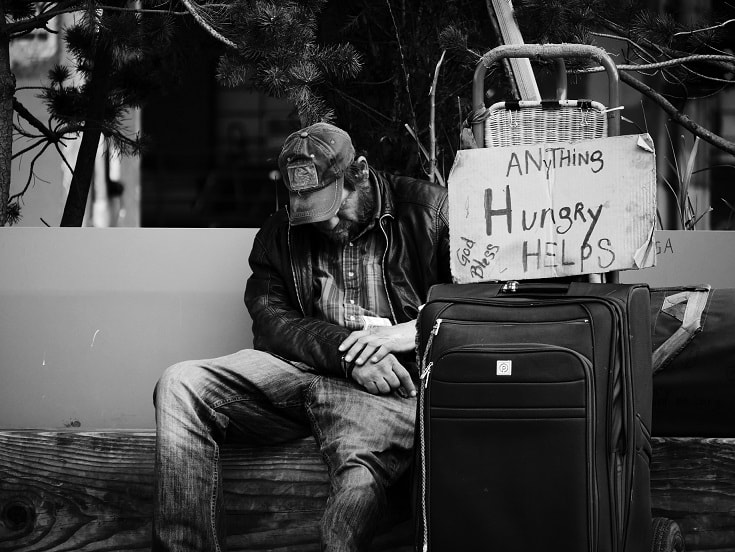 A beggar sitting next to a suitcase